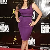 America in a purple Brian Reyes fold front dress, skinny black belt, and black peep-toes — ladylike perfection.
