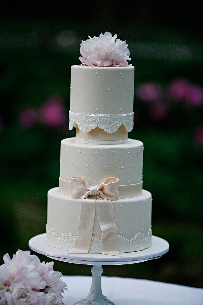 It's got pearls, it's got a bow, it's got a lace-like pattern, it's got flowers — yet this cake still manages to be sweet and romantic in the simplest way.  Photo by Marie Labbancz Photography via Style Me Pretty
