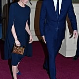 ‎Meghan Markle Carrying a Naeem Khan Armory Zodiac Clutch Bag in Leo Gold