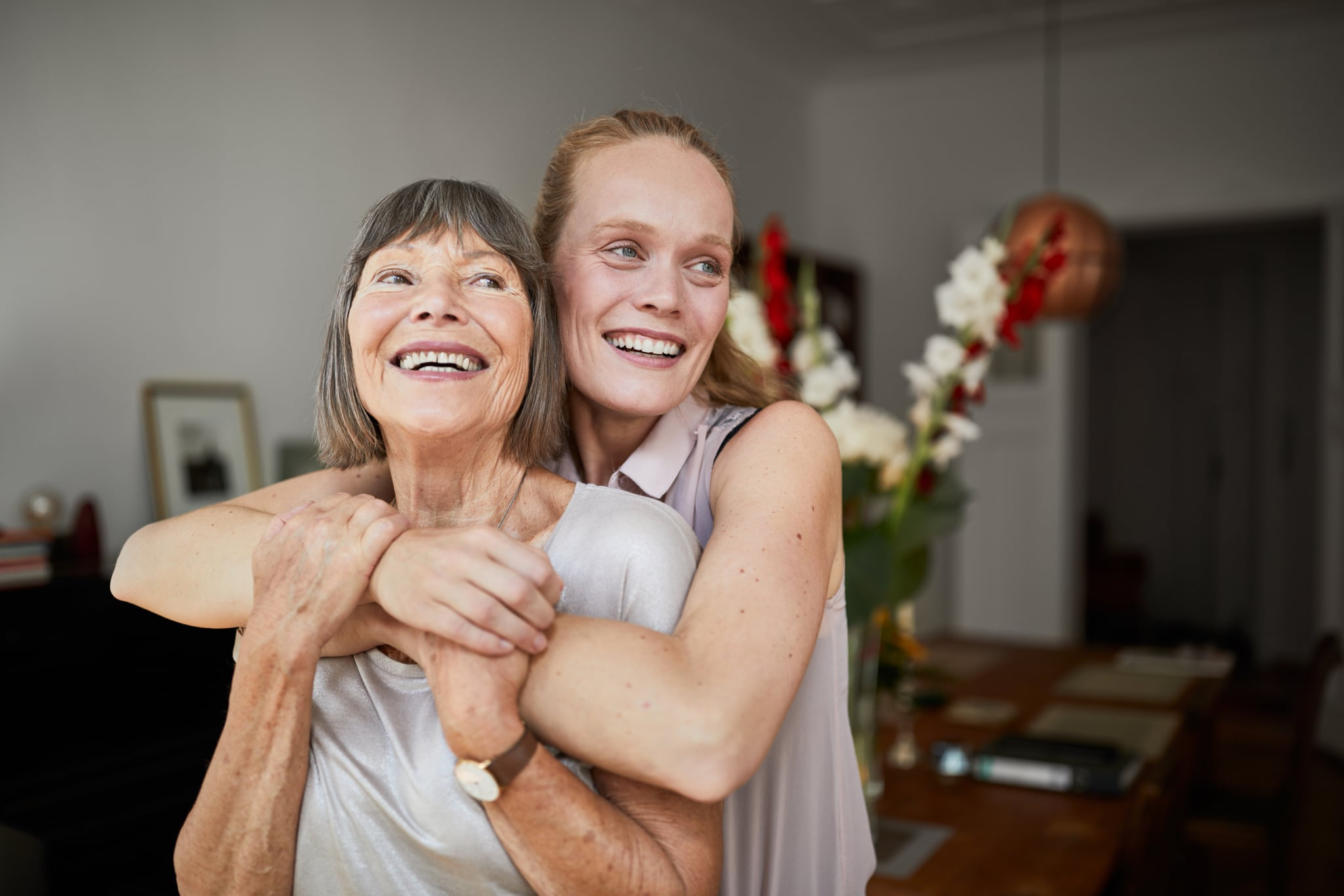 Cheerful mature woman embracing senior mother at home and looking away. Portrait of elderly mother and middle aged daughter smiling together.