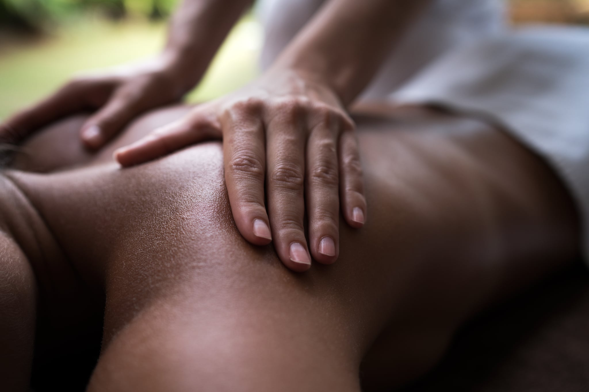 Close up of a human hand massaging woman's back.
