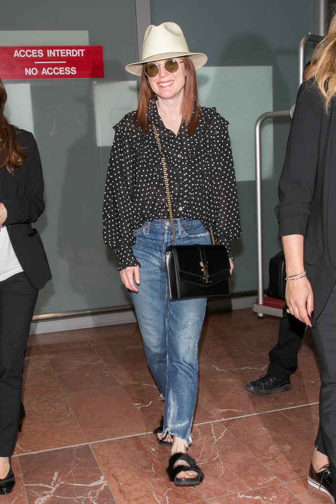 When she got off the plane in Nice, Julianne was wearing a chic yet comfortable travel outfit consisting of a polka-dot blouse, straight leg jeans, and flat, furry sandals. She accessorized her look with a fedora, round sunglasses, and a crossbody Saint Laurent bag.