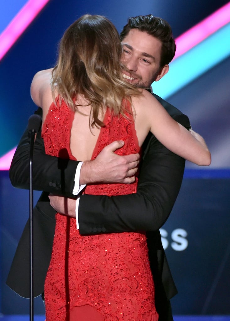 John Krasinski and Emily Blunt were all about the sweet PDA at Thursday night's Critics' Choice Awards. Not only did the cute couple crack each other up while walking the red carpet, but John actually popped out from backstage to hug Emily when she accepted the award for best actress in an action movie for her role in Edge of Tomorrow. See all the stars at the Critics' Choice Awards, and then take a look at John and Emily's best moments from the night — including John's GIF-worthy stage surprise!
