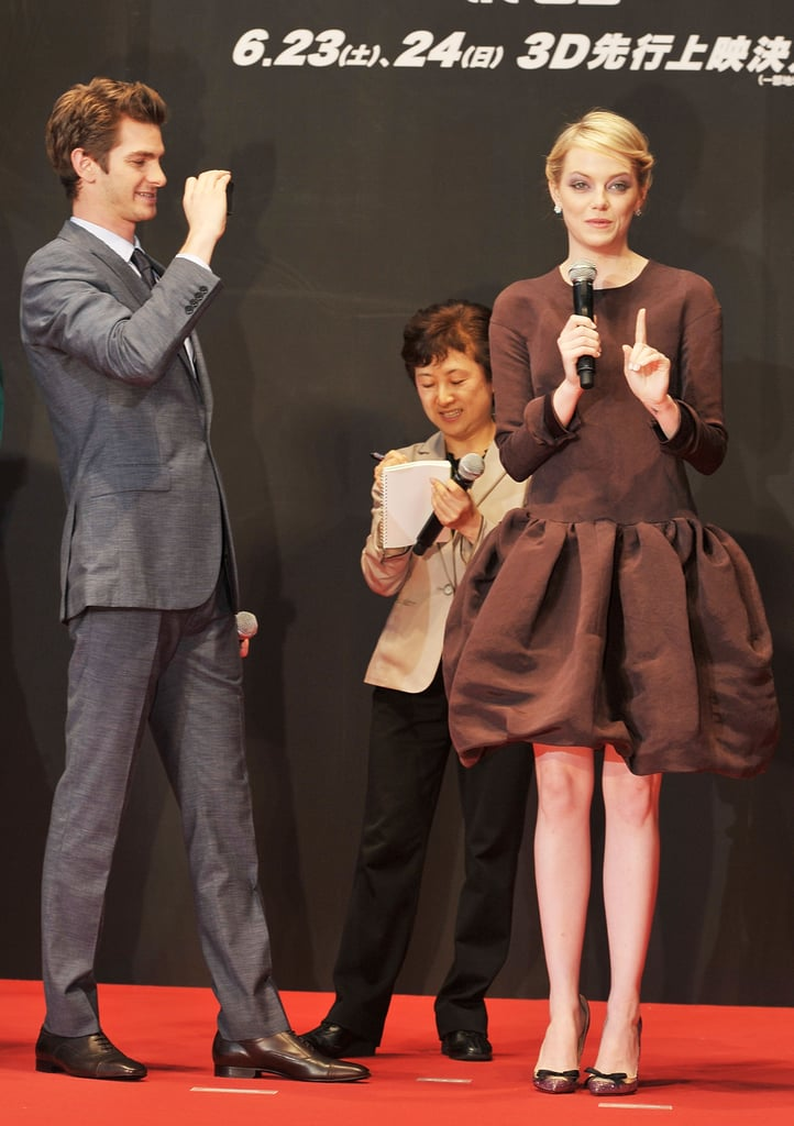 Andrew Garfield snapped photos of Emma Stone who spoke onstage at The Amazing Spider-Man premiere in Japan.