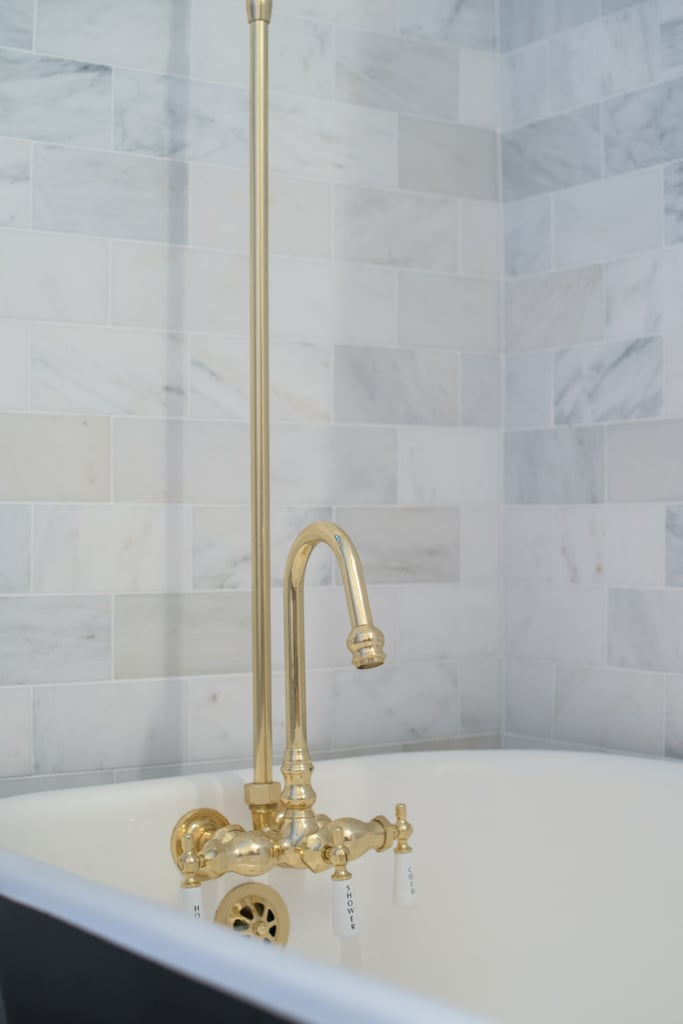 The glamorous brass hardware allows for the best of both worlds — a soaking tub that can also work for quick showers. Photo by Samantha Goh via Homepolish