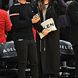 Chrissy attended a basketball game wearing a long black hoodie, striped shirt, and leather boots. She carried a white Balenciaga clutch.