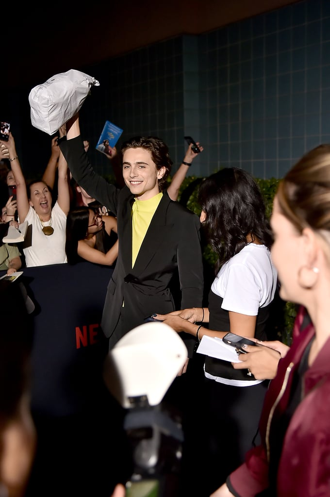 """A true monarch is someone who brings bagels on the red carpet. That's how I know Timothée Chalamet is a royal I can trust — even if he only plays one in movies. The 23-year-old actor greeted fans with a surprise snack at the NYC premiere of his Netflix film The King on Oct. 1, a sweet gesture in response to a fan's request on Twitter. I love a generous ruler!  In The King, Timothée plays Henry V opposite Joel Edgerton's Falstaff and Robert Pattinson's Dauphin. Timothée's real-life girlfriend, Lily-Rose Depp, also stars as Henry's wife Catherine. """"He just did a really great job,"""" Lily-Rose told Variety at the premiere. """"He really takes on his roles wholeheartedly, so it can only be super exciting and great to work with somebody like that. I think he did a really incredible job.""""   Keep reading to see videos from the shocked crowd, as well as photos from Timothée's night on the red carpet. Catch the movie in theaters on Oct. 11 and on Netflix starting Nov. 1. Long live the king!"""