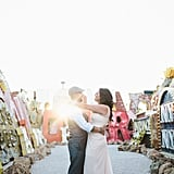 """""""I loved this image because of that perfect sun coming in through a retired neon sign in a graveyard for old signs of Las Vegas. A Neon Graveyard, which was such a unique experience. Each couple is so unique, and I love when they can show their uniqueness on their wedding day."""" — Gabriel Gastelum"""