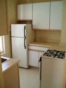A kitchen should be the hub of a house where people gather to enjoy food and wine. But in this box-shaped kitchen, there's not much room for several people.