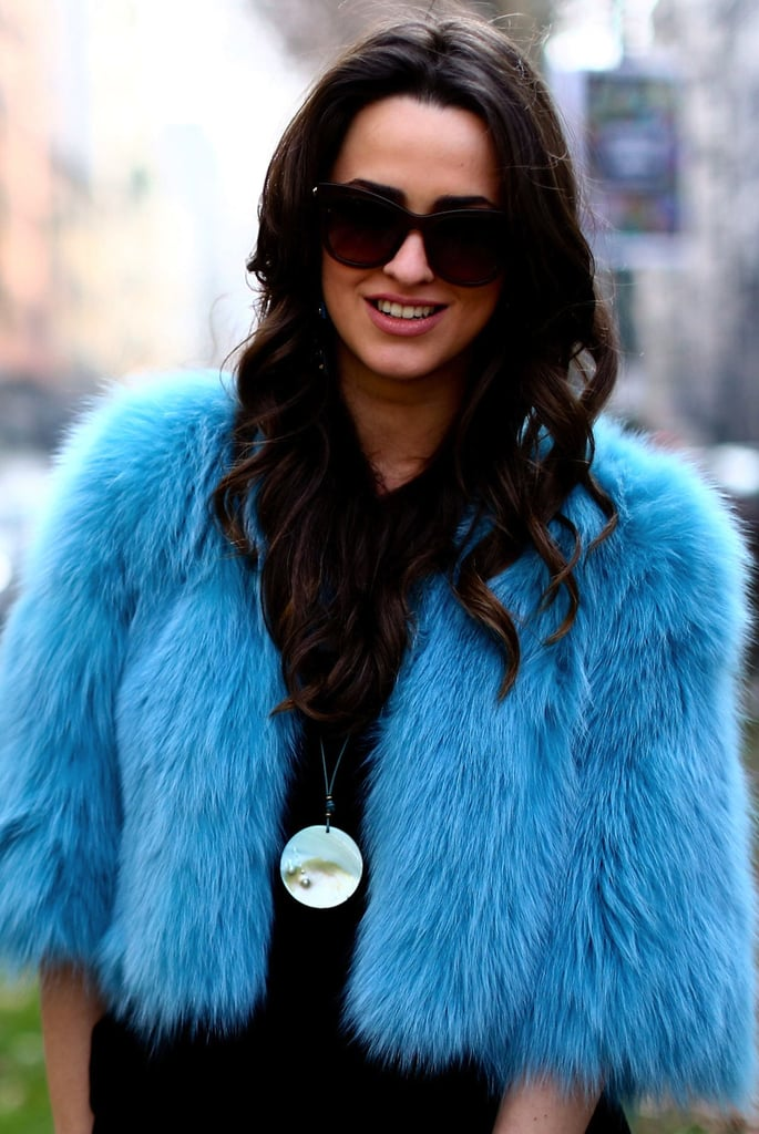 Dark shades and a shiny disc necklace tempered a bright blue jacket.