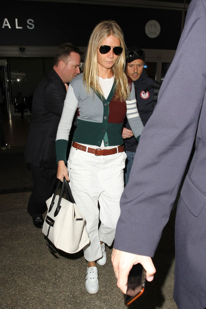 Gwyneth carried her white-and-black Céline bag at the airport, wearing a colorblock cardigan and baggy trousers.
