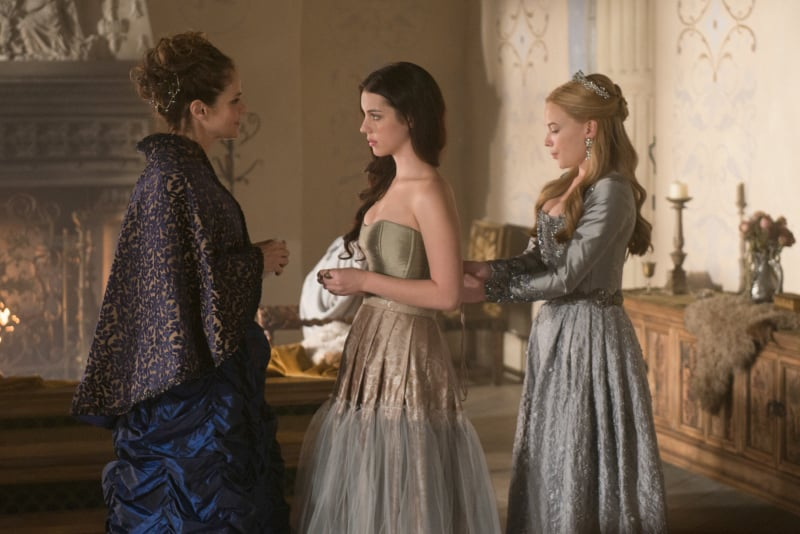 Greer (Celina Sinden) cinches Mary (Adelaide Kane) into her undergarments.
