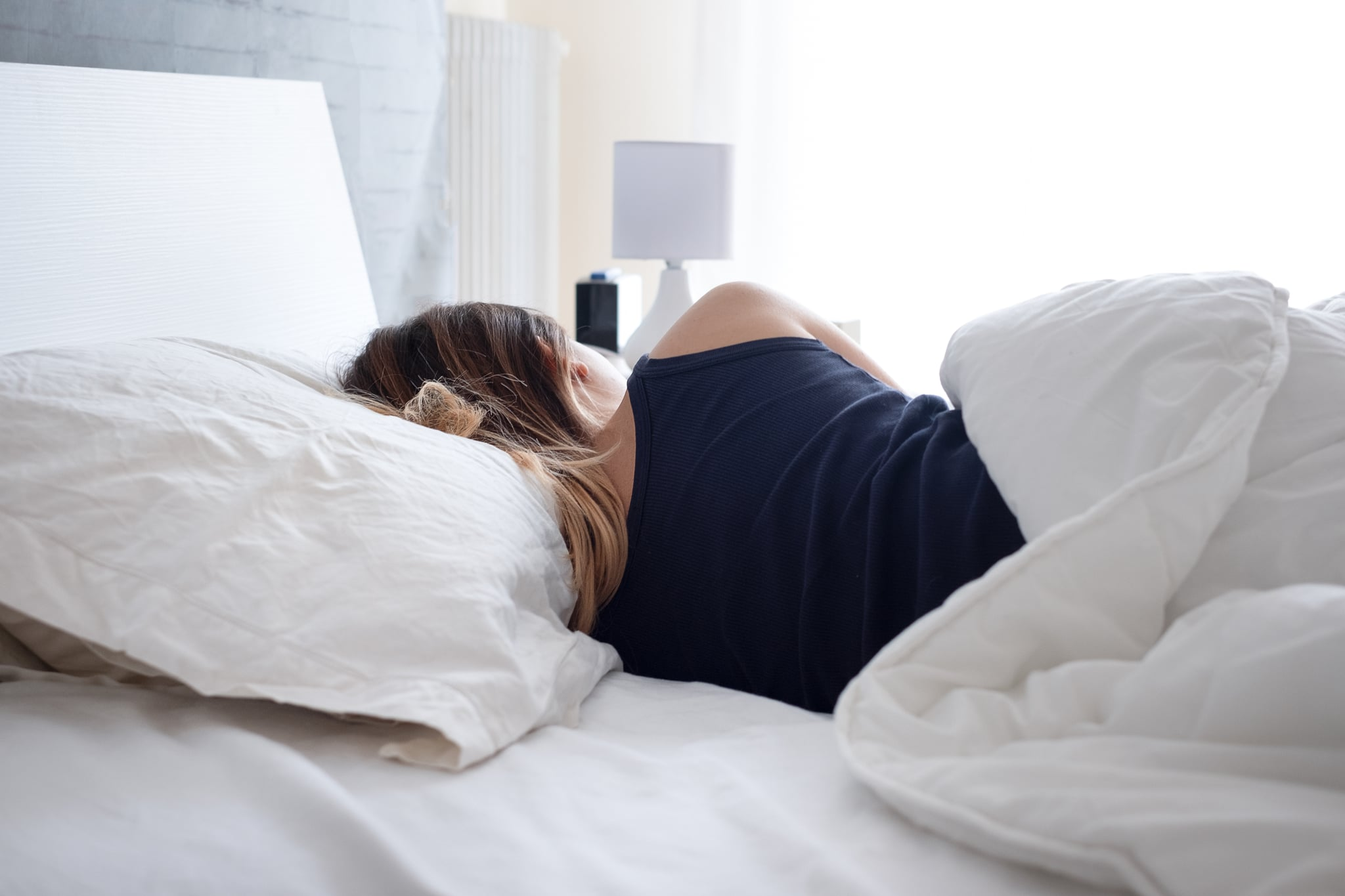 Back view of woman sleeping comfortable in bed