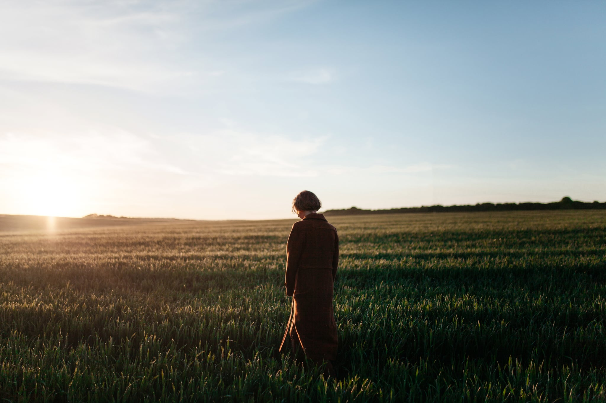 Young Caucasian woman in red coat  walking  in the field at sunset