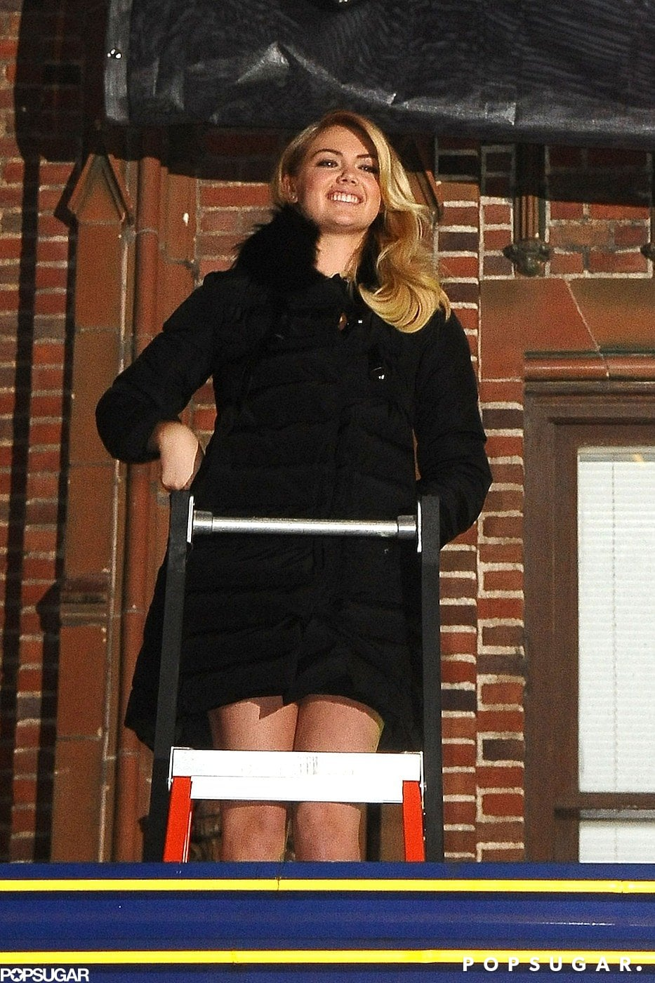 Kate Upton stood above the studio to unveil her cover.