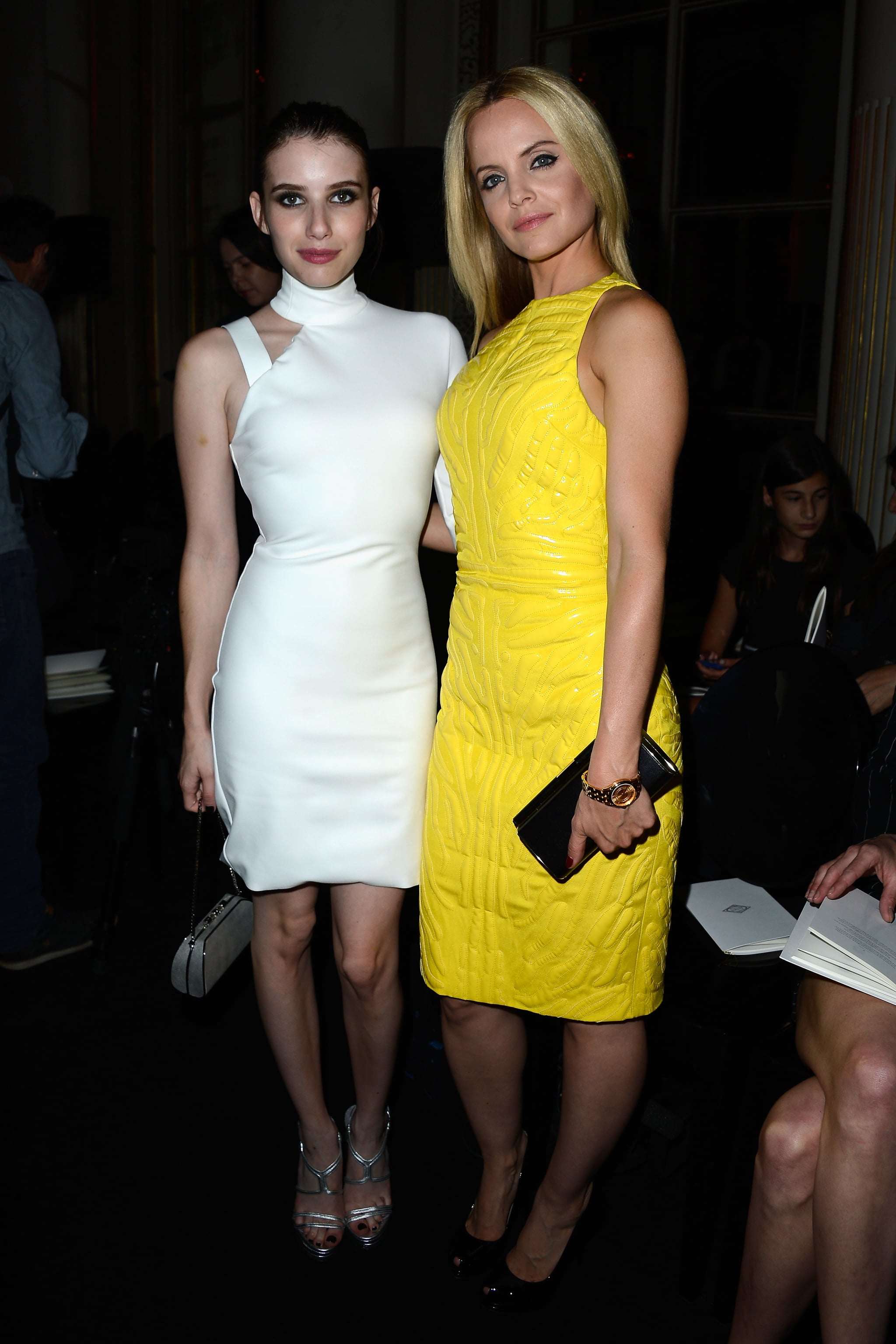 Emma Roberts and Mena Suvari posed together in the front row of Versace's couture show in Paris. Emma opted for a white one-shouldered dress, while Mena picked a bright yellow number, both by Versace.