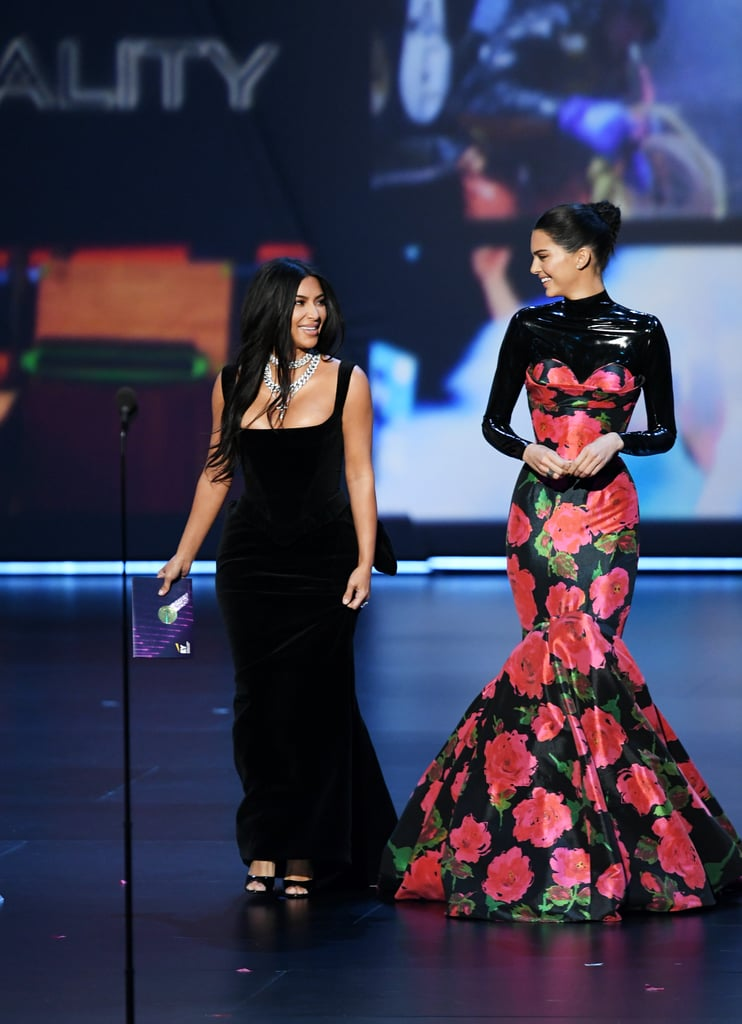 Kim Kardashian and Kendall Jenner turned the Emmy Awards purple carpet into a sisters' night out on Sunday, and they looked damn good doing it. The Keeping Up With the Kardashians stars chose complementary black dresses for the show, each putting their own spin on a uniquely sexy look.  Kim opted for a skintight black velvet dress with a square neckline, ruffled detailing in the back, and layered silver necklaces, while Kendall wore a pink floral Richard Quinn gown (straight off the runway!) over a latex Vex turtleneck. Clearly, these sisters know there's more than one way to make an LBD work! Keep reading to see more angles of their Emmys looks ahead.      Related:                                                                                                           These Sexy Emmys Red Carpet Dresses Are So Hot, They Deserve an Award of Their Own