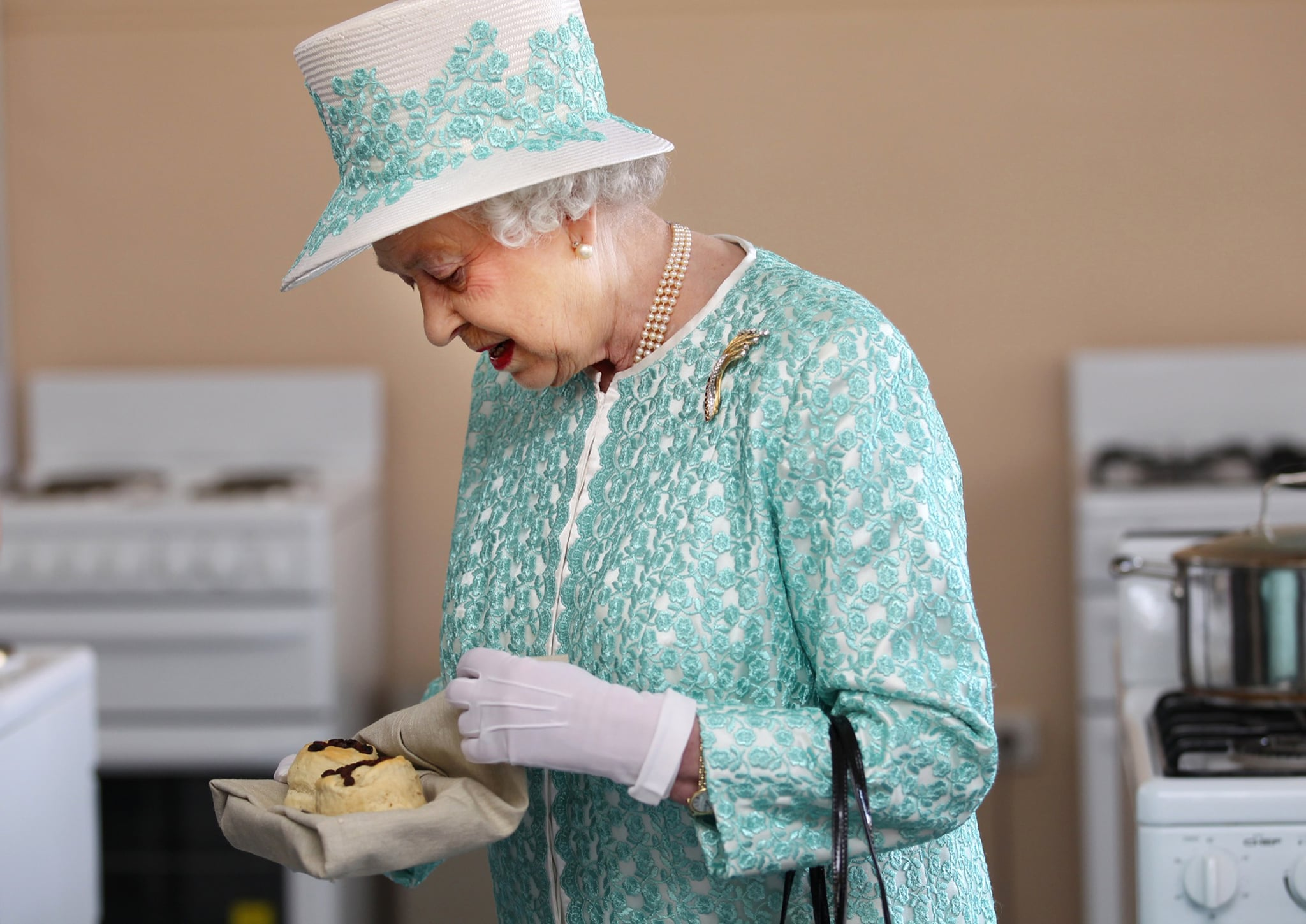 Britain's Queen Elizabeth II looks at homemade scones as she visits the kitchen at Clontarf Aboriginal College in Perth on October 27, 2011. The queen, who arrived in Perth on October 26, will officially open the 54-nation Commonwealth Heads of Government Meeting (CHOGM) on October 28 where revamping succession to the British throne will be discussed, concluding a 10-day tour of her antipodean realm.    AFP PHOTO / POOL / SHARON SMITH (Photo credit should read SHARON SMITH/AFP via Getty Images)