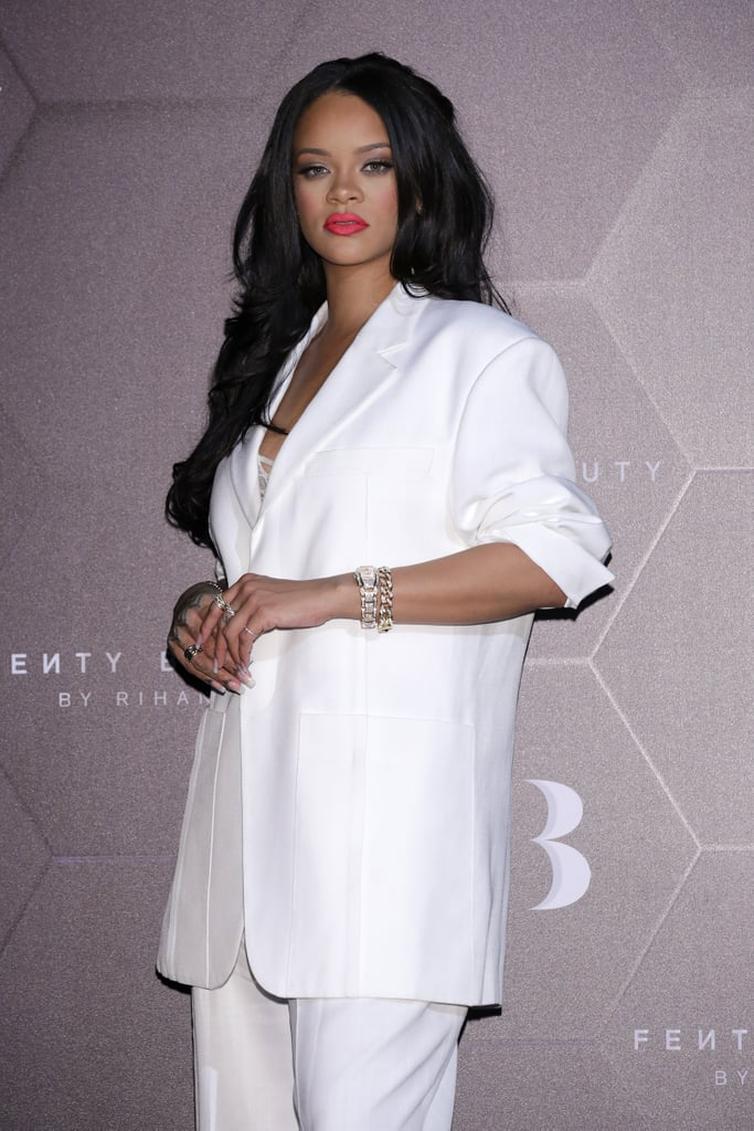 Rihanna is rapidly becoming a multi-industry tycoon, and she's got the wardrobe to match. The singer-turned-entrepreneur recently attended a Fenty Beauty event in Seoul, South Korea, wearing an all-white oversize Jacquemus suit and matching pumps. Peeking out beneath the suit was a metallic lace bodysuit — from her own Savage x Fenty lingerie brand, of course. Rihanna's stunning outing comes shortly after she staged her second-ever lingerie show during New York Fashion Week, which featured choreographed dances, music performances, and plenty of celebrity appearances both on and off the runway. What's more, the entire show will be available to stream on Amazon Prime Video come Sept. 20. With so many boss moves being made, why not wear a boss suit? See pictures ahead.