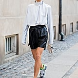 Try it all by styling a ladylike silk blouse with edgy leather shorts and sporty performance sneakers to boot.
