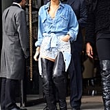 An oversize chambray shirt — with another denim shirt tied around her waist — some seriously spike-enhanced denim shorts, and sexy thigh-high leather boots made up Rihanna's London hotel departure style in February 2012.