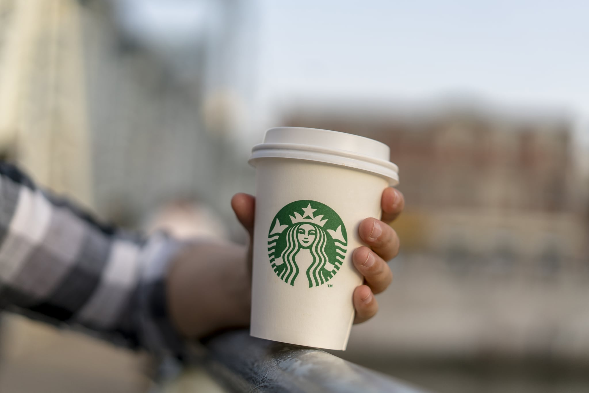 TIANJIN, CHINA - 2017/04/29: A girl holds a Starbucks coffee cup on a bridge.  Starbucks cup. According to the report of the second quarter in 2017, the revenue of Starbucks was $5.3 billion, and the sales growth rate of both the global and the United States are 3%, while in China the number is 7%, which might become the main contributor to the growth of Starbucks in 2017. (Photo by Zhang Peng/LightRocket via Getty Images)