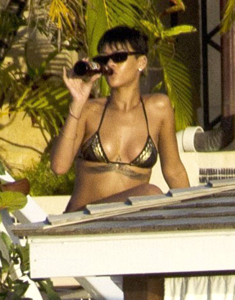 "Less than 24 hours after performing ""Diamonds"" during last night's season finale of The Voice, Rihanna was spotted off the coast of Barbados yesterday. She slipped into a sexy gold bikini and relaxed under the sun with a beer in hand. She's back at home in Barbados ready to spend the holidays with friends and family after a busy year of topping the charts, touring the globe, and launching a new fragrance.  While Rihanna was born and raised in the small Caribbean island, she now calls California her home away from home. In fact, Rihanna just purchased a $12 million mansion with seven bedrooms and nine baths in LA's exclusive Pacific Palisades neighborhood. Her management company, Roc Nation, must have noticed she needed a sports car for her new garage and graciously gifted Rihanna a brand-new Porsche 911."