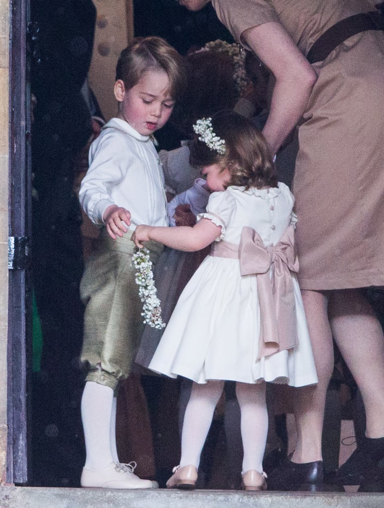 Prince George helped his little sister with her flower girl wreath as they prepped to walk down the aisle at Pippa's wedding.