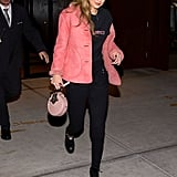 Gigi stuck to a pink theme with her mini circle handbag and Burberry coat while out in NYC. The star kept the rest of her outfit pitch black with a Paradised t-shirt and black jeans.
