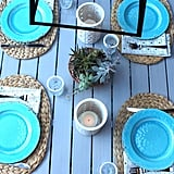 Tip #3: Set a Stylish Table Make any outdoor table look effortlessly elegant with just a few items. Instead of bothering with a fussy tablecloth, choose place mats with an interesting shape and texture. These natural fiber place mats ($24 for a set of four) are superversatile — not to mention wrinkle- and stain-proof.  Top them with colorful plates, like these rustic melamine options ($42 for a set of four). I love that these look like antique earthenware but are actually light and shatter-proof.  Instead of buying and arranging flowers, add a potted succulent to the table for a pop of fresh greenery.  Finish the look with a couple of ceramic outdoor table lanterns (old, similar version here). Fill them with battery-operated candles ($8) and you'll get the look and flicker of real candlelight without having to worry about them blowing out — or worse, catching fire.
