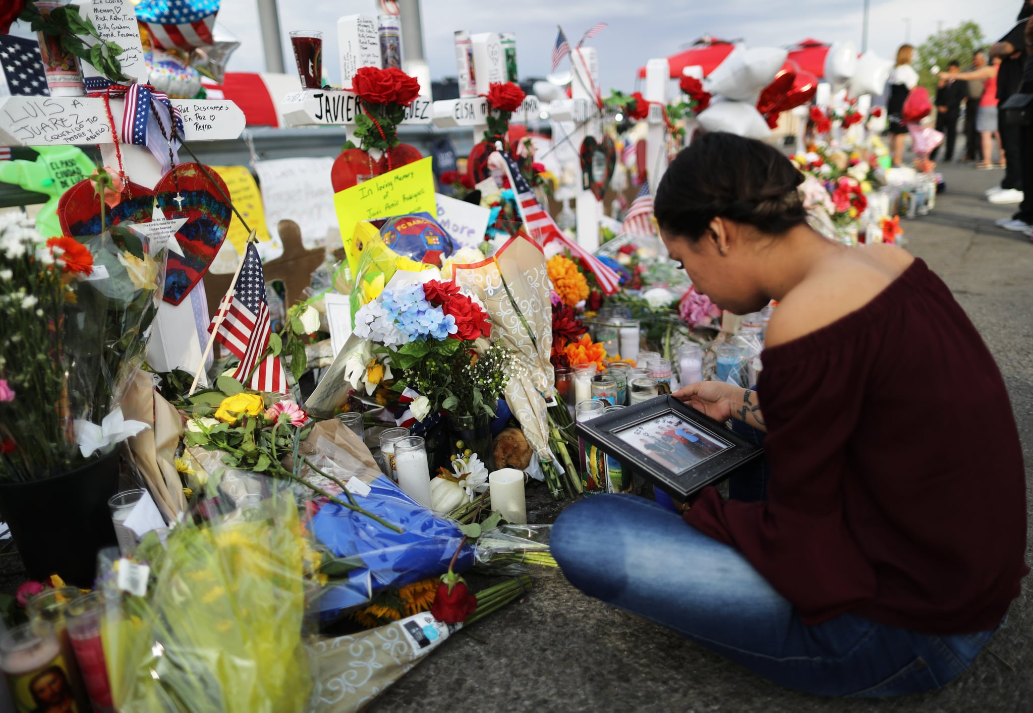 EL PASO, TEXAS - AUGUST 06: Yamileth Lopez holds a photo of her deceased friend Javier Amir Rodriguez at a makeshift memorial for victims outside Walmart, near the scene of a mass shooting which left at least 22 people dead, on August 6, 2019 in El Paso, Texas.  Rodriguez was a sophomore at Horizon High School and was killed in the shooting. A 21-year-old white male suspect remains in custody in El Paso, which sits along the U.S.-Mexico border. President Donald Trump plans to visit the city August 7.  (Photo by Mario Tama/Getty Images)