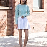 With a sweet sweater and cool flats.