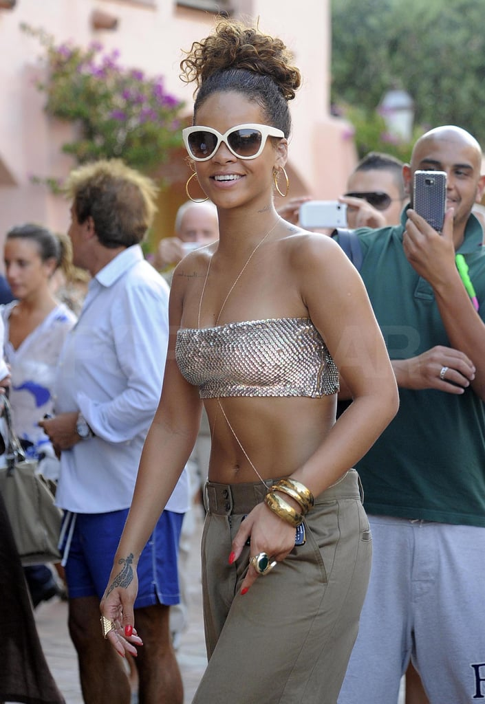 "Rihanna made the most of her final hours in Sardinia, Italy, yesterday, first stopping at Prada then partying late into the night with girlfriends. During her latest shopping spree, Rihanna stepped out wearing a sequin bikini top, but earlier in the week she showed off her sexy body in a bright blue bikini and toasted champagne with friends wearing a colorful cutout one-piece. Rihanna's been sailing around the Mediterranean for the past week, but even on vacation she managed to release her latest video, ""Cheers (Drink to That)."""