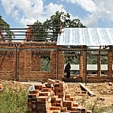 I blame it on being a builder's daughter, but seeing the school construction sites, on the third day of our trip, had a huge an impact on me. The first we visited was Kasomolo, estimated to be completed in May 2018, and offering 500 educational places (including staff quarters, a bio-gas kitchen and amphitheatre). The schools are beautiful, the bricks are full of colour, the elevated rooves (which were being put on the day of our visit) let in so much natural light and the sustainable design is beyond smart: they are electricity-free, the black board is built into the bricks, the outside walls are stepped to provide a bench, there's no glass in the windows (glass is expensive to replace) but instead, wooden shutters. The surrounding African countryside is breathtaking.