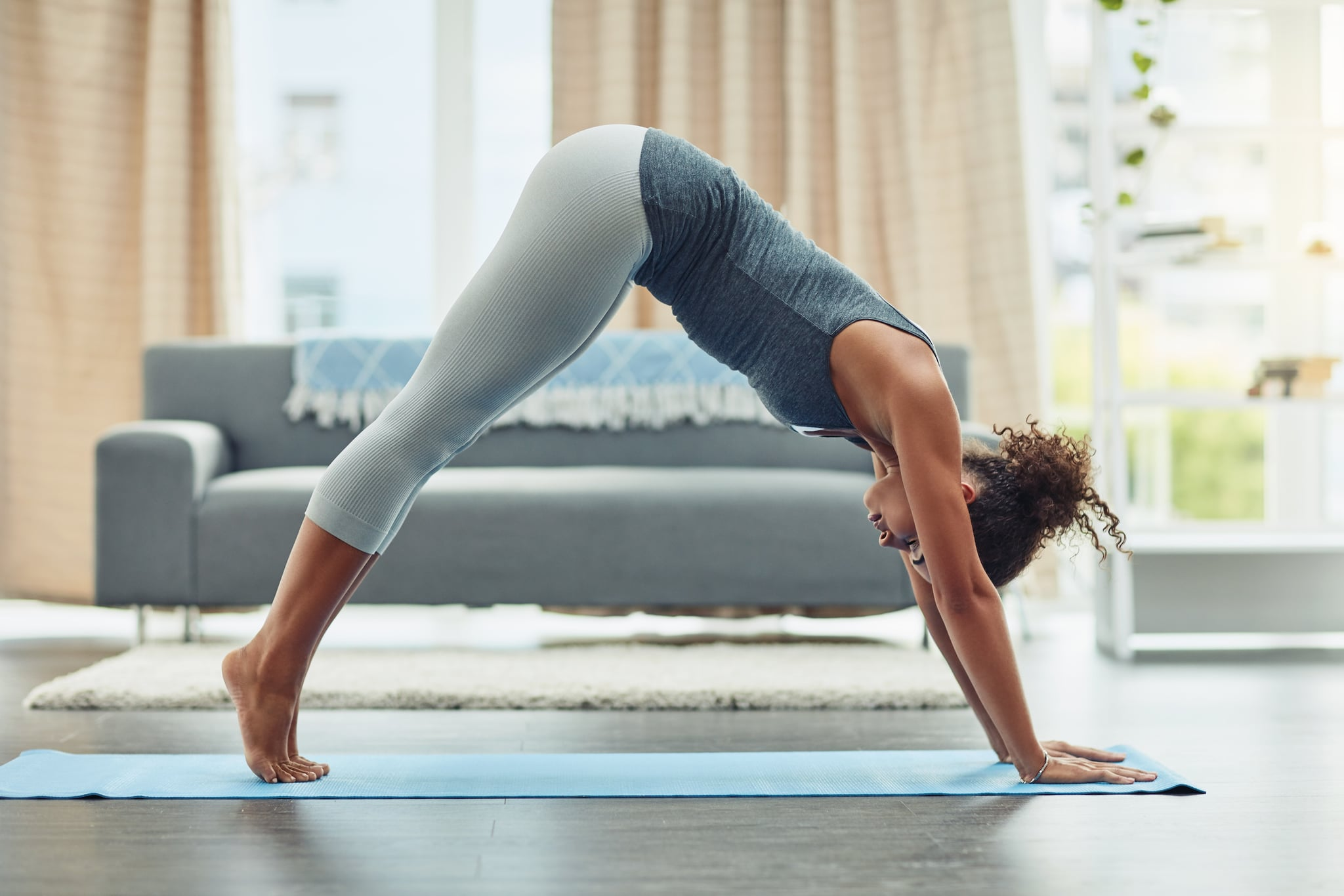 Shot of an attractive young woman practicing yoga at home