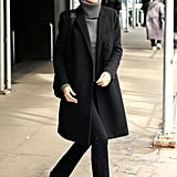 Gisele Bündchen kept her look low key with a grey polo neck, black coat, and black trousers.