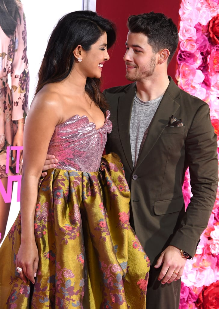 Just in case you weren't already aware, Nick Jonas and Priyanka Chopra are really freaking cute together. On Monday, the newlyweds continued to flaunt their romance as they attended the premiere of Priyanka's upcoming film, Isn't It Romantic, which also stars Liam Hemsworth, Rebel Wilson, and Adam DeVine. Nick looked sharp in a brown suit, while Priyanka looked like modern-day Marie Antoinette in a pink and yellow gown.  Fittingly, the pair were incredibly romantic as they laughed on the red carpet and stared lovingly into each other's eyes. At one point, Nick couldn't help but step back and appreciate his wife's beauty as she posed for photographers. Forget heart-shaped chocolate and teddy bears, all I want for Valentine's Day this year is someone to look at me the way Nick looks at Priyanka.