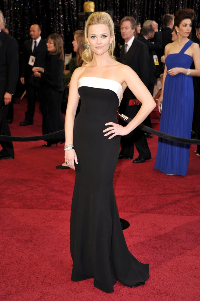 Reese Witherspoon looked classy and elegant on the red carpet at the Oscars. She's on hand as a presenter at the awards, and fans are holding out hope that her Water For Elephants costar Robert Pattinson will also show his handsome face at some point. Reese, who coordinated her black and white strapless gown with a bouncy ponytail and her engagement ring, beamed for photographers before heading inside. Vote on her look and many more with our love it or hate it polls!