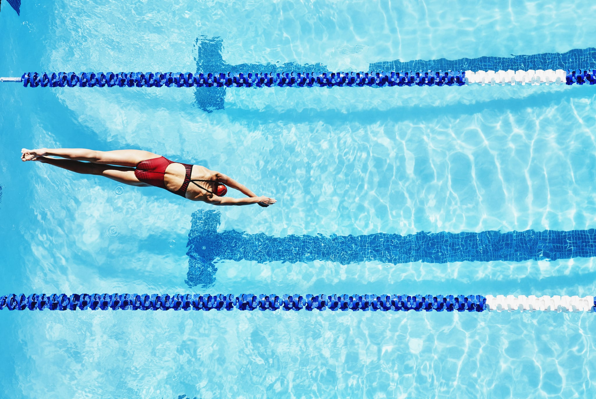 Female competitive swimmer diving into outdoor pool overhead view
