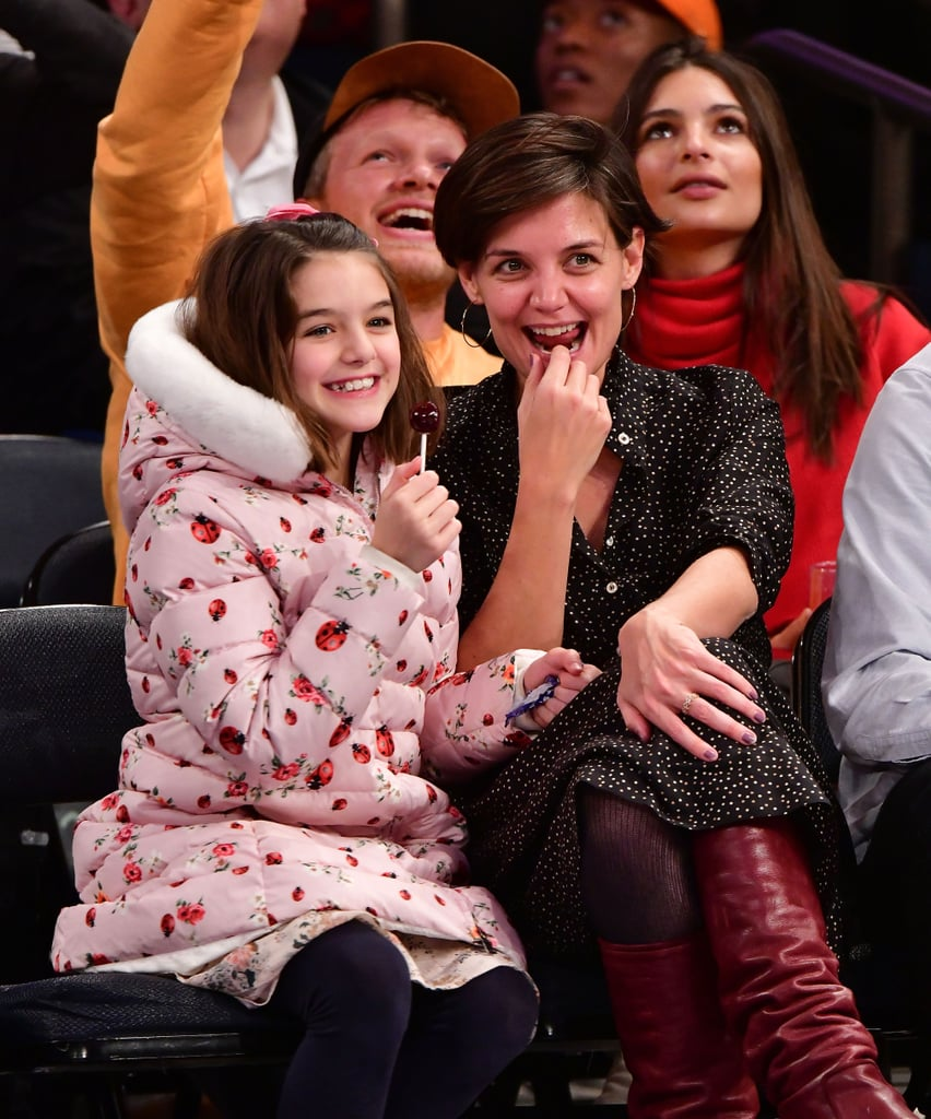 Katie Holmes and Suri Cruise made an appearance at the Knicks game in NYC on Saturday night. The 38-year-old actress and her 11-year-old daughter turned the fun evening into a bonding experience as they sat courtside and cuddled up next to each other. Suri wore a pink coat adorned with ladybugs all over meanwhile, Katie kept things casual in a polka-dotted outfit and burgundy boots. One person notably missing from their super cute outing was Katie's boyfriend of four years, Jamie Foxx.  While the low-profile couple has yet to make an official appearance together, they were spotted holding hands on the beach in September, confirming their romance. Katie recently celebrated Jamie's 50th birthday in LA and showed up to support the Oscar-award winning actor at the opening of his NYC eyewear store earlier this month. The doting-mom appeared in good spirits at the game with her mini-me which comes just weeks after their festive date night at Z100's Jingle Ball concert. Read on to see more photos of their sweet outing ahead.