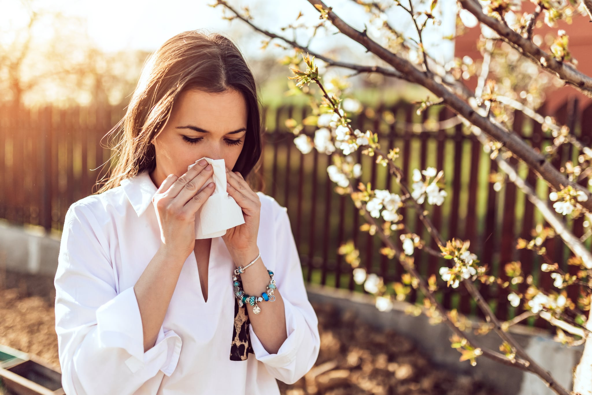 Attractive young adult woman coughing and sneezing outdoors. Sick people allergy or virus influenca concept.