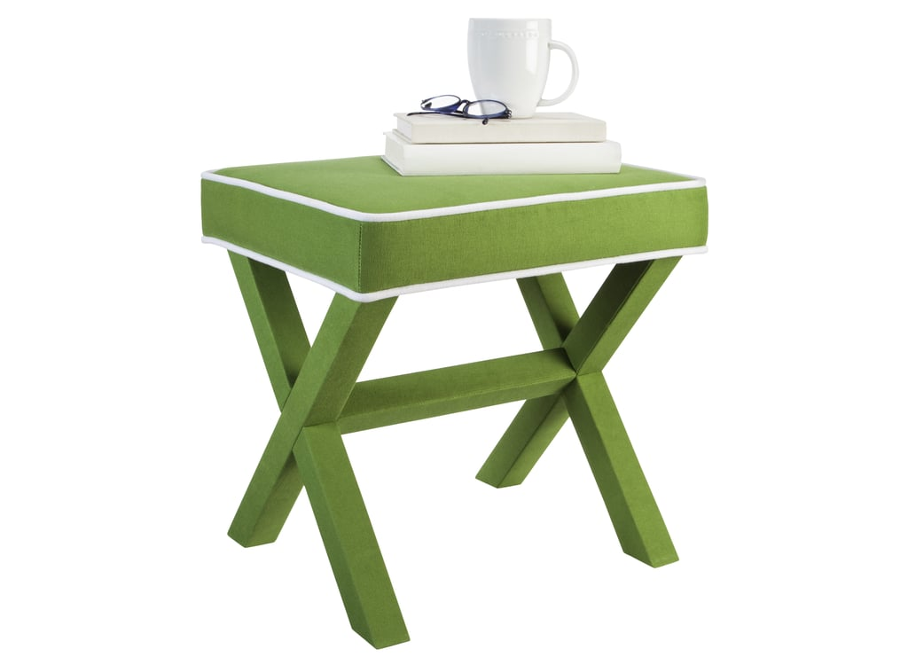 Grassy green fabric and white piping add a playful touch to this x-base ottoman ($60).