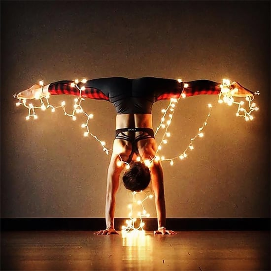 Women Doing Yoga Wrapped in Christmas Lights