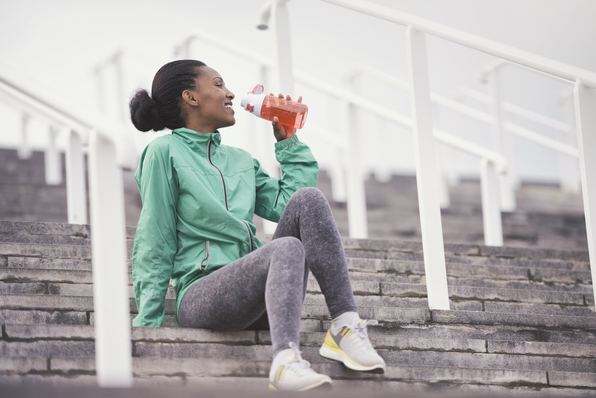 Low angle view of a young athletic woman taking a break from running exercises, drinking water from a plastic refillable bottle.