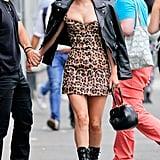 Wearing a button-through leopard dress by Miaou with a Saint Laurent leather jacket, Giuseppe Zanotti boots, a Gabriela Hearst bag, and Alaïa sunglasses.