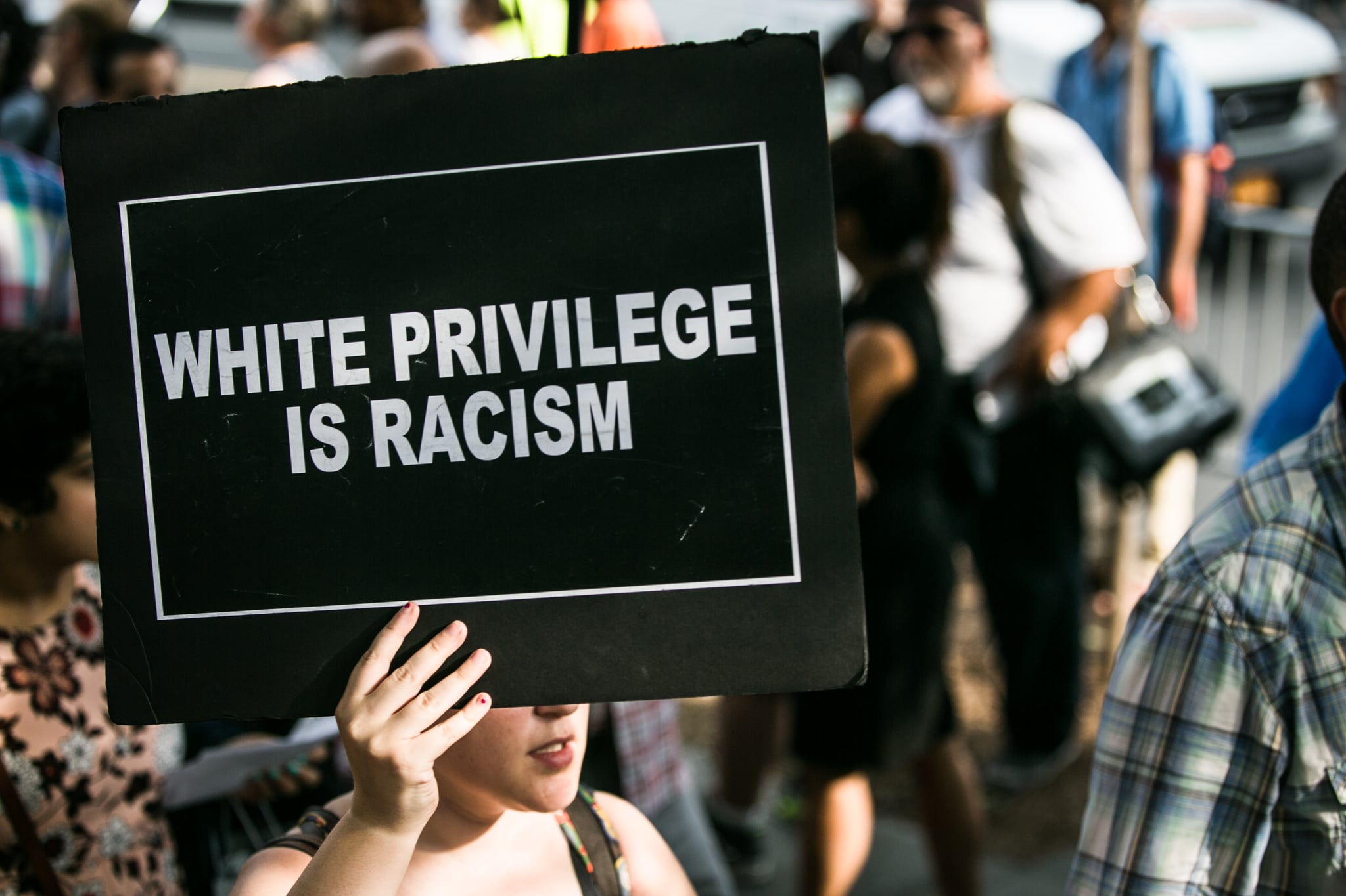"A protestor holds a sign reading, ""WHITE PRIVILEGE IS RACISM"" on July 7, 2016. Thousands rallied calling for an end to the epidemic of unsanctioned police murder occurring primarily in black communities across the United States. (Photo by Karla Ann Cote/NurPhoto via Getty Images)"