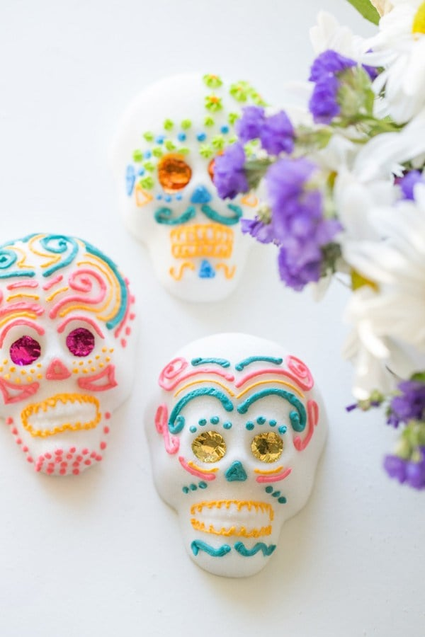 One of the biggest traditions families incorporate when hosting a Day of the Dead gathering and building an altar is making homemade sugar skulls. The classic recipe is simple: sugar, meringue powder, and water.  Once you have your molds ready, you can go plain, adorn them with traditional designs, or add special touches and details to make your skulls truly unique for the person they are meant to honor. We've rounded up a variety of recipes with unique decorating options, and even a couple of different flavor selections, if you choose to make them edible.       Related:                                                                                                           10 Easy Yet Original DIY Ideas For Día de los Muertos