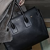 And you can't just carry any old bag when you're rocking Chanel sneakers! She opted for the classic black Saint Laurent Sac de Jour bag that we've spotted Angelina Jolie carrying.