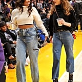 Jessica attending a Lakers game with Gabrielle Union in matching outfits: turtleneck sweaters, wide-legged jeans, and heels.