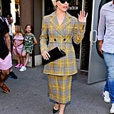 Wearing a vintage-inspired suit with black heels.
